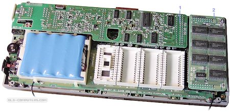 """The upper side of the logic board holds the battery, the four ROM sockets as well as two piggi-back cards, the Serial interface card (1) and the 128 KB RAM card (2)."""